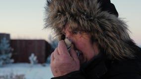 Het bejaarde in Jasje en Bonthoed in de Winter veegt Zijn Neus met een Zakdoek af stock video