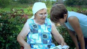Het bejaarde leest het boek aan zijn kleinzoon stock videobeelden