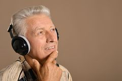 Het bejaarde luistert aan muziek in hoofdtelefoons Stock Afbeeldingen