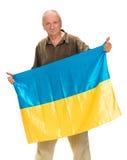 Het bejaarde met Oekraïense vlag in zijn handen het tonen beduimelt omhoog Stock Afbeelding