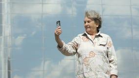 Het bejaarde neemt foto's gebruikend zilveren smartphone stock video
