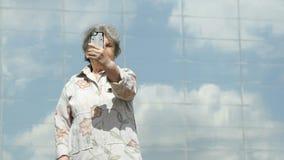 Het bejaarde neemt foto's gebruikend zilveren smartphone stock videobeelden