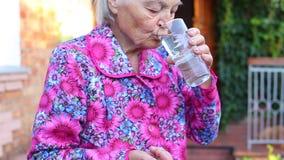Het bejaarde oudere wijfje houdt de tabletten water drinkt stock videobeelden