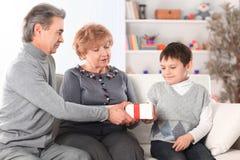Het bejaarde paar geeft een gift aan hun kleinzoon op zijn verjaardag royalty-vrije stock afbeelding