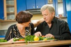 Het bejaarde paar koken bij keuken stock afbeeldingen