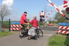 Het bejaarde paar op fietsen wacht bij spoorwegovergang Stock Foto