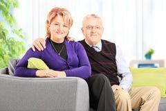 Het bejaarde paar stellen thuis gezet op een bank Royalty-vrije Stock Afbeeldingen