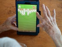 Het bejaarde ` s overhandigt het Spelen Patience op een Tablet royalty-vrije stock foto's