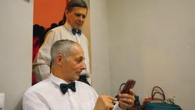 Het bejaarde toont iets aan zijn vriend in mobiele telefoon stock video