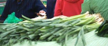 Het bejaarde verkoopt of koopt producten op landbouwersmarkt hand met geld voor de aankoop Verkoop van vruchten en groenten bij royalty-vrije stock fotografie