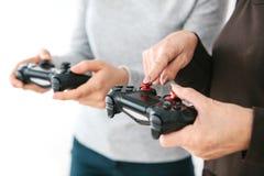 Het bejaarde vraagt het jonge meisje hoe te om de bedieningshendel voor videospelletjes te gebruiken en toont haar vinger op de k Royalty-vrije Stock Foto's