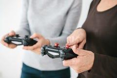Het bejaarde vraagt het jonge meisje hoe te om de bedieningshendel voor videospelletjes te gebruiken en toont haar vinger op de k Stock Afbeeldingen