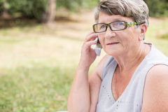 Het bejaarde vrouwelijke spreken op mobilofoon Stock Foto's