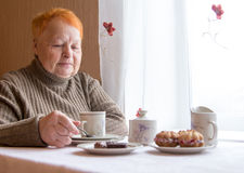 Het bejaarde zit bij lijst en drinkt thee met cakes Stock Afbeeldingen