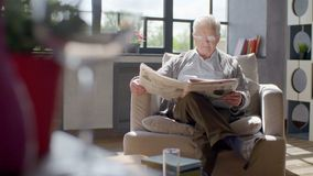 Het bejaarde zit in een stoel en een lezing een krant in een moderne flat stock video