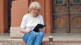 Het bejaarde zit op de stappen en het gebruiken van tabletcomputer met oortelefoons en drinkt koffie De uitstekende bouw op de ac stock video
