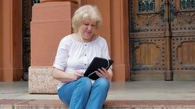 Het bejaarde zit op de stappen en het gebruiken van tabletcomputer met oortelefoons De uitstekende bouw op de achtergrond stock videobeelden