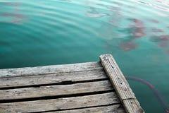 Het bekijken het blauwgroene water van een houten dok stock foto