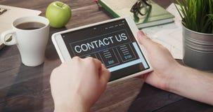 Het bekijken contact ons Web-pagina die digitale tablet bij bureau gebruiken stock footage
