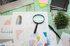 Het bekijken de groeigrafiek met vergrootglas De grafieken, brengt in kaart royalty-vrije stock fotografie