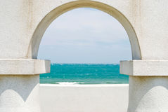 Het bekijken de oceaan door boogdeur Stock Fotografie
