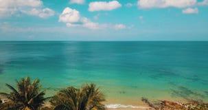 Het bekijken door tropische boombladeren het mooie lagunezeewater tijdens de zomerdag stock videobeelden