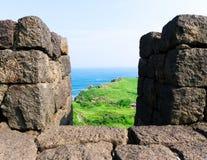 Het bekijken door Vulkanische Steenpijlers Groene Gras en Oceanen Stock Afbeeldingen