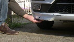 Het bekijken een beschadigd voertuig De mens inspecteert autoschade na een ongeval stock foto's