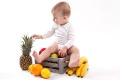 Het bekijken fruit leuke glimlachende baby op witte achtergrond onder fru Stock Foto