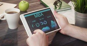 Het bekijken MBA-verslagen die digitale tablet bij bureau gebruiken stock footage