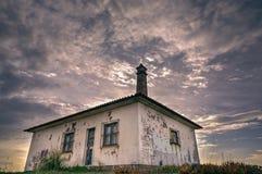 Het bekijken omhoog een oud verlaten huis tegen een dramatische hemel Royalty-vrije Stock Afbeeldingen