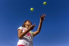 Het bekijken omhoog meisje het jongleren met Royalty-vrije Stock Afbeeldingen