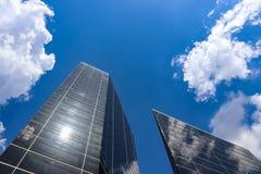 Het bekijken omhoog moderne gebouwen met bezinningen en een zeer blauwe hemel met pluizige wolken royalty-vrije stock foto's