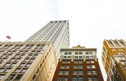 Het bekijken omhoog overladen art decogebouwen met een Amerikaanse vlag die op vliegen stock afbeeldingen