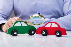 Het bekijken Rode en Groene Auto door Vergrootglas stock afbeeldingen