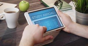 Het bekijken studie in het buitenland Web-pagina die digitale tablet bij bureau gebruiken stock video