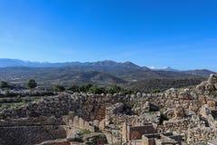 Het bekijken uit meer dan het heuvelfort in Mycenae Griekenland en het museum en het parkeerterrein en over landbouwgrond en olij stock fotografie