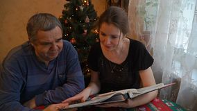 Het bekijken van een album van de familiefoto stock videobeelden