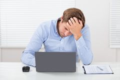 Het beklemtoonde Bureau van Zakenmanusing laptop in Stock Foto's