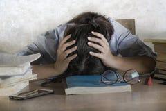 Het beklemtoonde en gefrustreerde tienerstudent werken met handboeken en laptop computer aan bureau overweldigde en putte het leu royalty-vrije stock afbeeldingen