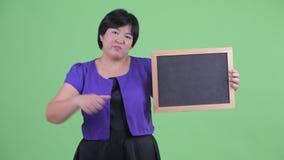 Het beklemtoonde jonge te zware Aziatische bord van de vrouwenholding en het geven beduimelen neer stock video