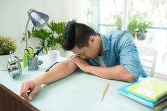 Het beklemtoonde overwerkte mens bestuderen slaperig op bureau stock afbeeldingen
