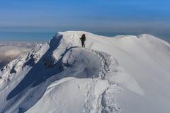 Het beklimmen op berg in de winter Stock Afbeelding