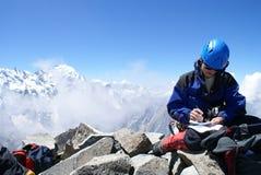 Het beklimmen schrijft een bericht op de bovenkant van berg Stock Foto's
