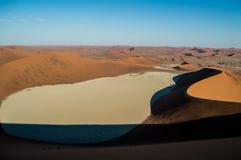 Het beklimmen van Big Daddy Dune, die de Zoute Pan van Sossusvlei, Woestijn bekijken Royalty-vrije Stock Foto's