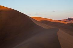 Het beklimmen van Big Daddy Dune tijdens Zonsopgang, Woestijnlandschap in Dawn Stock Afbeeldingen