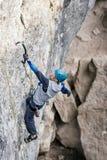 Het beklimmen van de mens op een rots stock foto's