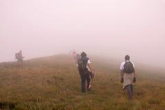 Het beklimmen van de piek in mist royalty-vrije stock afbeelding