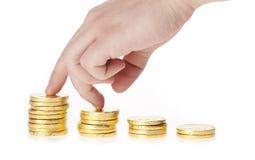 Het beklimmen van hand op gouden muntstuktrap Stock Foto's