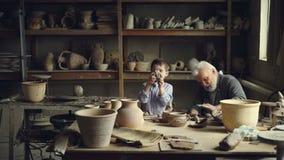 Het bekwame kind helpt zijn hogere grootvader professionele pottenbakker om klei voor met de hand gemaakte ceramische cijfers te  stock videobeelden
